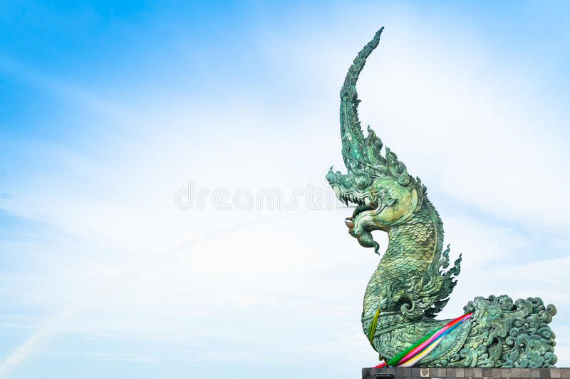 L'eau de pulvérisation de statue de Naga vers la mer avec le fond de ciel bleu image libre de droits