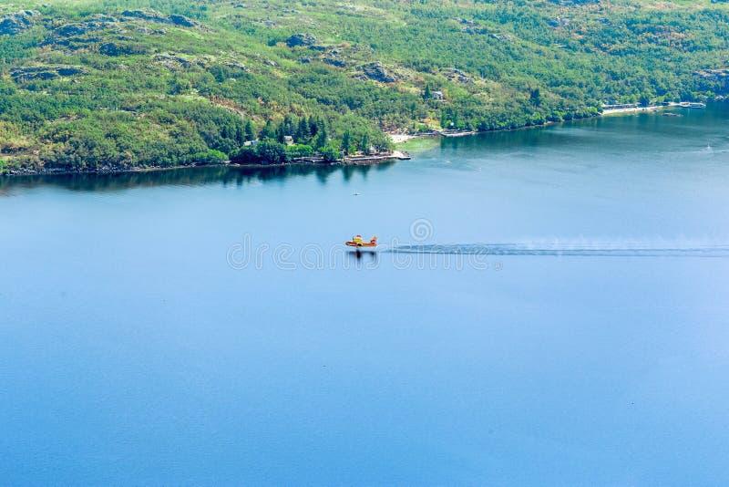 L'eau de rassemblement plate de sapeur-pompier sur le lac pour éteindre un incendie de forêt images stock