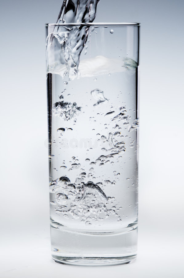 l'eau de ruisseau pleuvante à torrents minérale en verre images stock