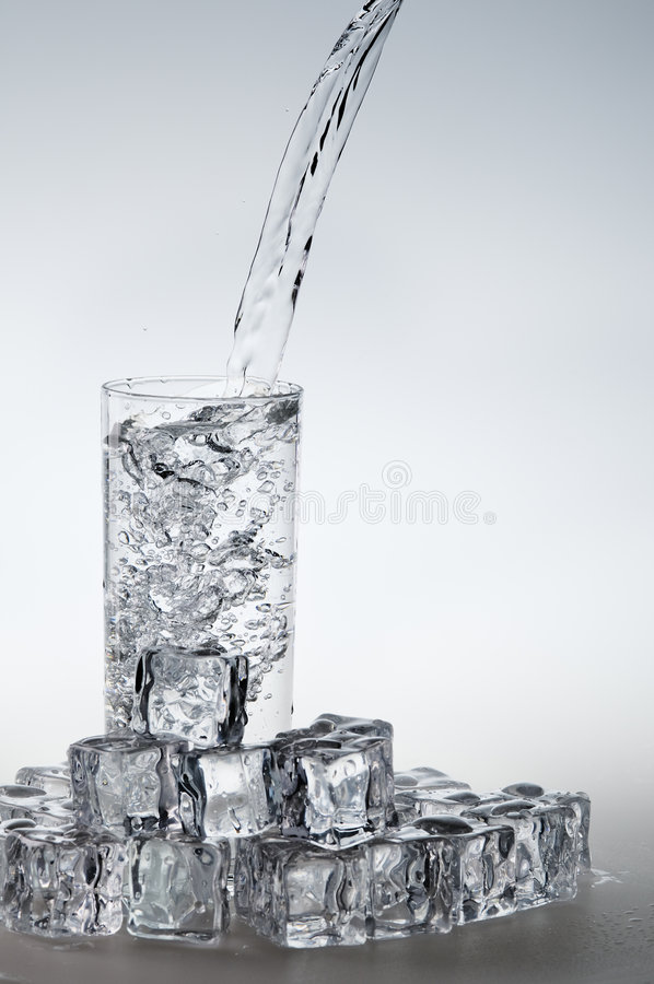 l'eau de ruisseau pleuvante à torrents minérale en verre photographie stock libre de droits