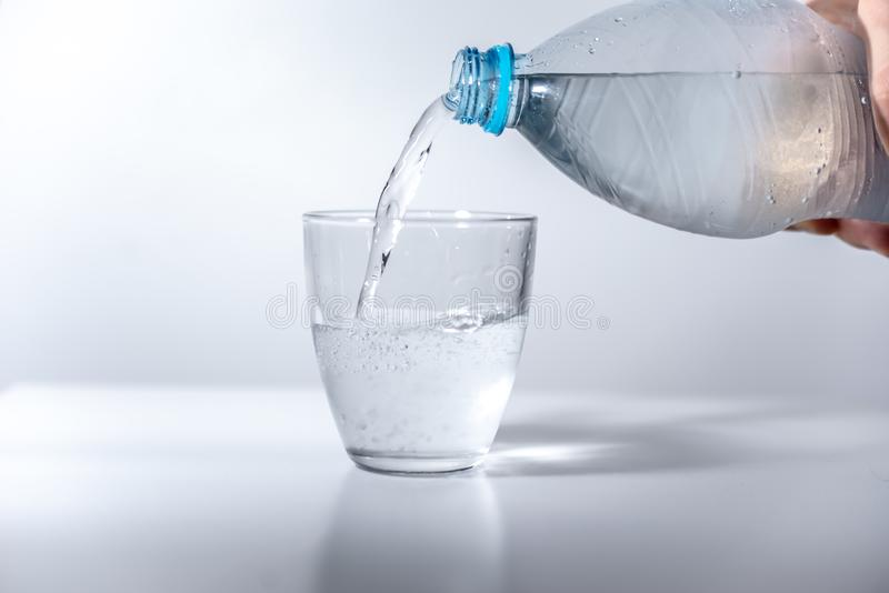 L'eau de scintillement de versement de main de la bouteille en plastique au verre rempli avec de l'eau minéral froid sur la surfa photo stock