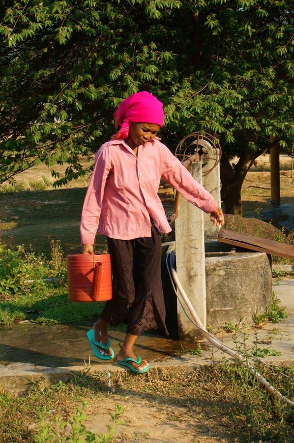 L'eau de scoop de personnes du puits d'eau photo stock