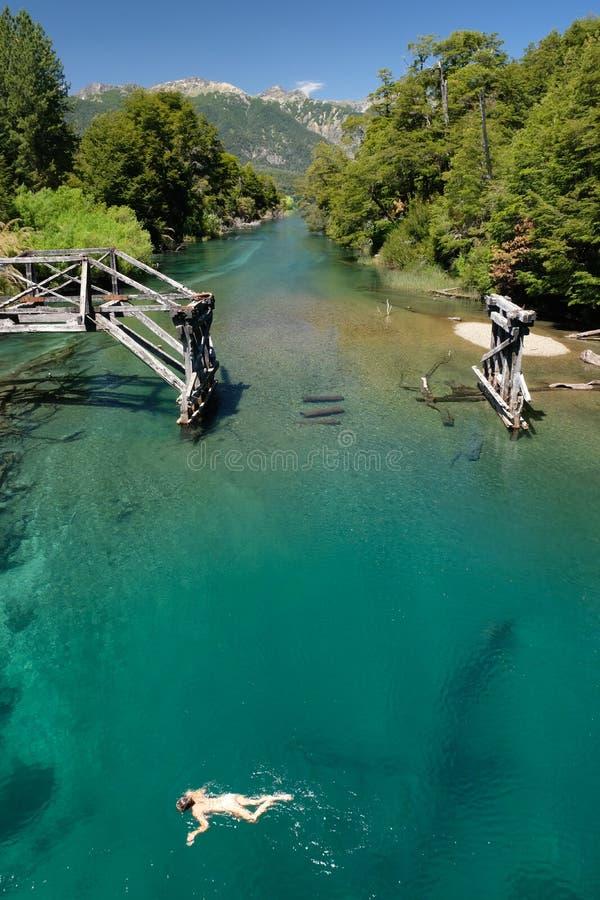 L'eau de Teal la rivière Green dans le Patagonia, Argentine avec la vieille natation 2 de pont et de fille photo stock