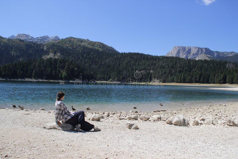 L'eau de turquoise du lac, de la for?t de pin et des montagnes Fond de stup?faction avec le touriste de fille de nature s'asseyan photographie stock libre de droits