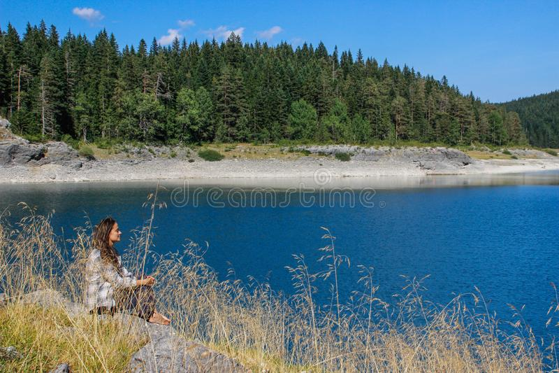 L'eau de turquoise du lac, de la for?t de pin et des montagnes Fond de stup?faction avec le touriste de fille de nature s'asseyan photo libre de droits
