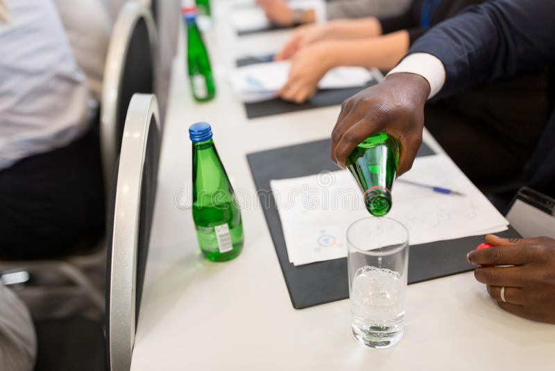 L'eau de versement d'homme d'affaires au verre à la conférence image stock