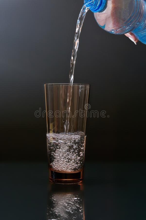 L'eau de versement d'une bouteille d'animal familier dans un gobelet en verre sur un fond foncé images stock