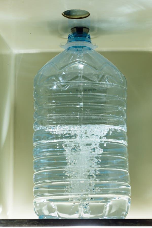 L'eau de versement dans la bouteille avec le distributeur de l'eau photographie stock libre de droits