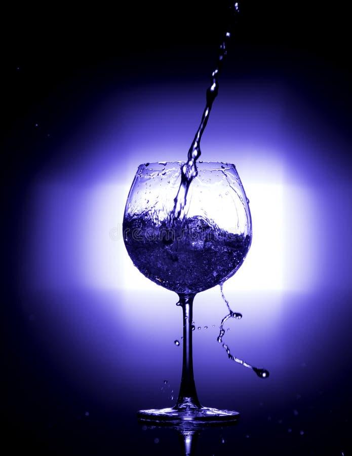 L'eau de versement dans le verre de vin avec l'équilibre blanc bleu de fond noir images stock