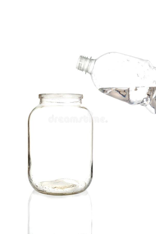L'eau de versement dans un pot en verre vide sur un fond blanc images stock