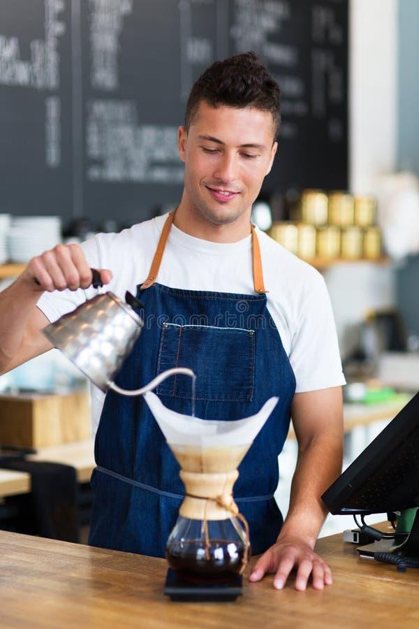 L'eau de versement de barman dans le filtre de café photo libre de droits