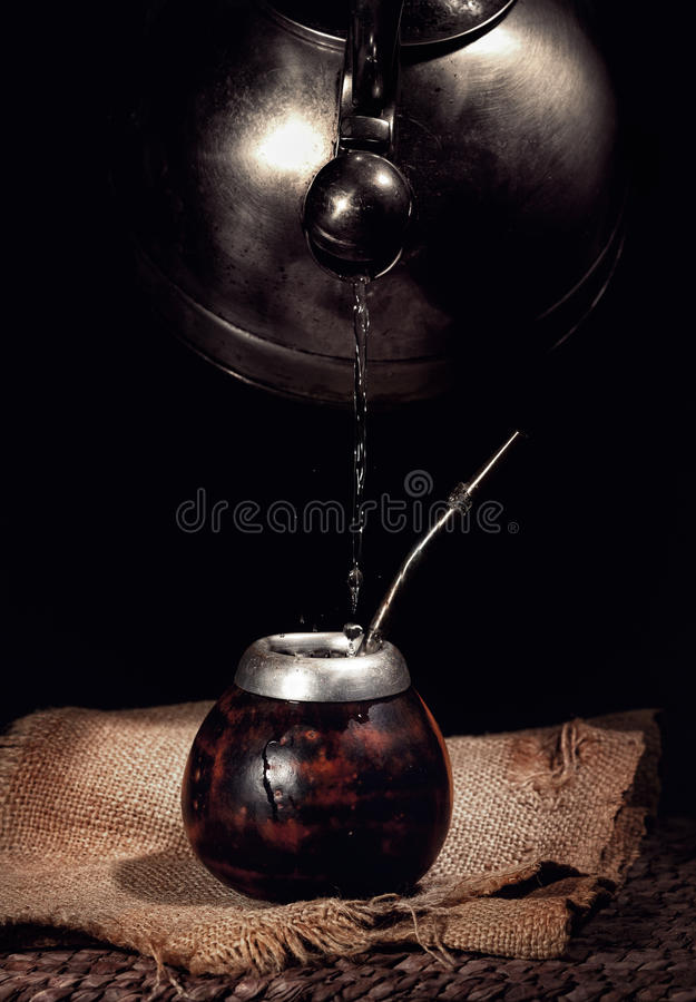 L'eau de versement de la bouilloire dans la calebasse photographie stock