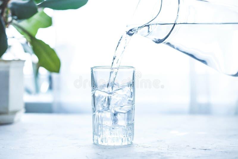 L'eau de versement sur le verre avec de la glace sur la table blanche images stock
