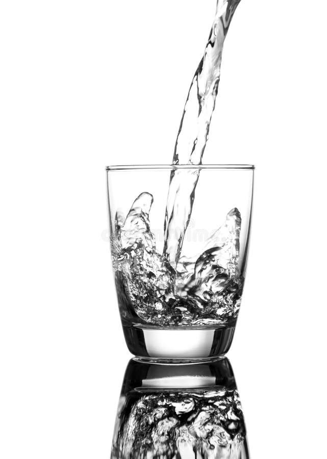 L'eau de versement sur un verre photographie stock libre de droits