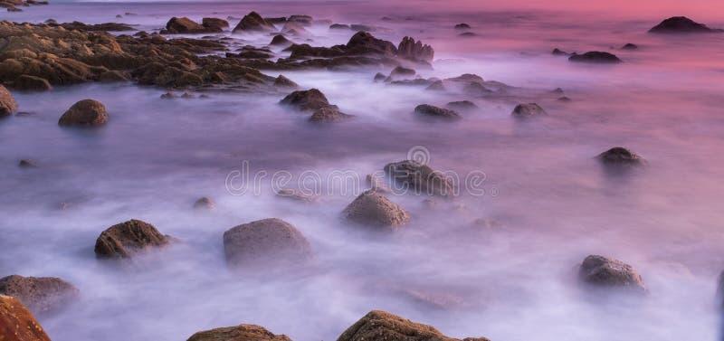 L'eau des vagues se brisant contre les roches photographie stock