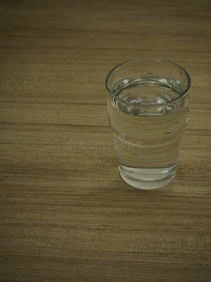 L'eau en verre sur la table en bois images stock