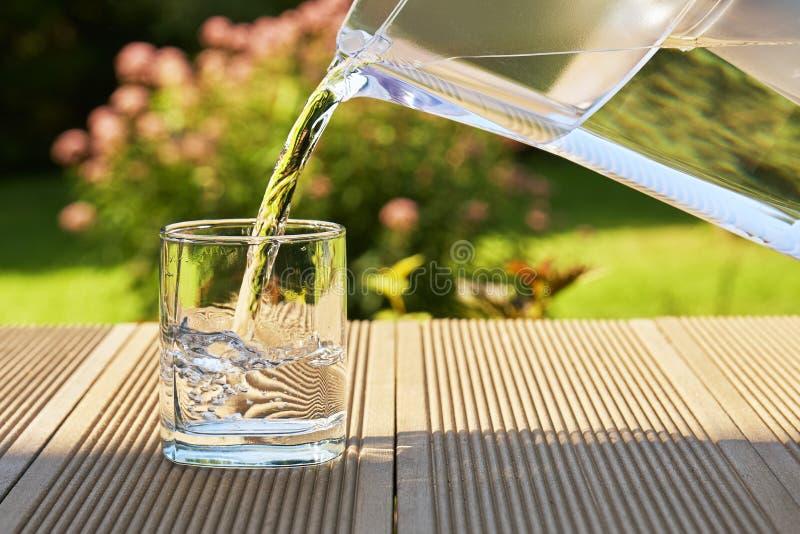 L'eau filtrée claire de versement d'une cruche de filtration de l'eau dans un verre dans le jardin vert d'été dans un jour d'été  photos libres de droits