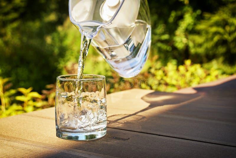 L'eau filtrée claire de versement d'une cruche de filtration de l'eau dans un verre dans le jardin vert d'été dans un jour d'été  photographie stock libre de droits