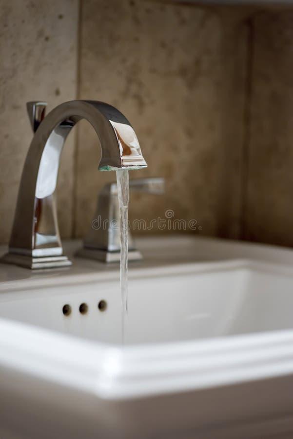 l'eau fonctionnant au robinet de salle de bains photos stock