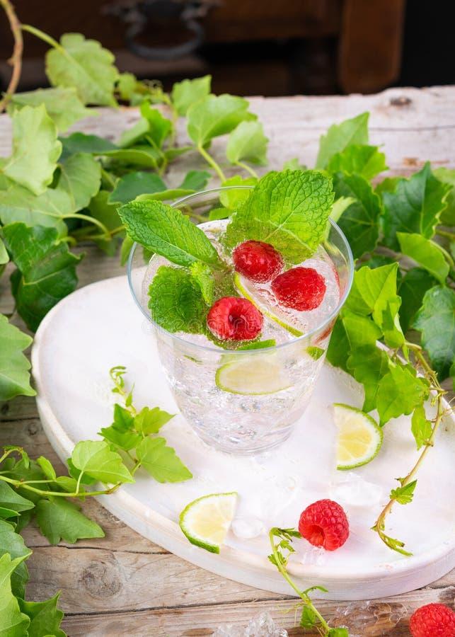 L'eau froide fraîche de boissons, glaçons, menthe poivrée, chaux, framboise sur une table rustique Réception en plein air extérie image stock