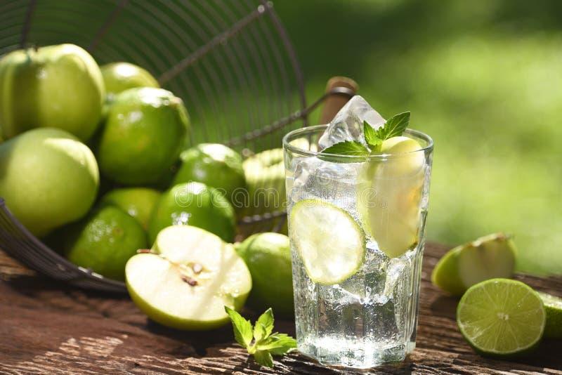 L'eau infusée avec la chaux et pomme en verre sur le fond en bois et de nature images libres de droits