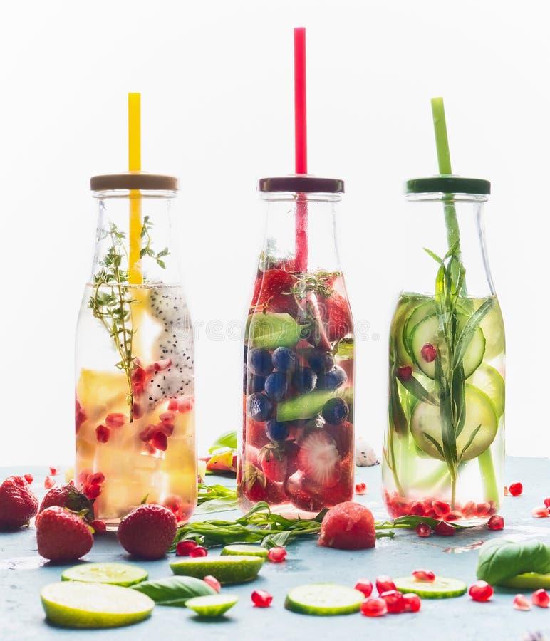 L'eau infusée dans des bouteilles avec la paille et les ingrédients de boissons sur le fond blanc, vue de face image libre de droits