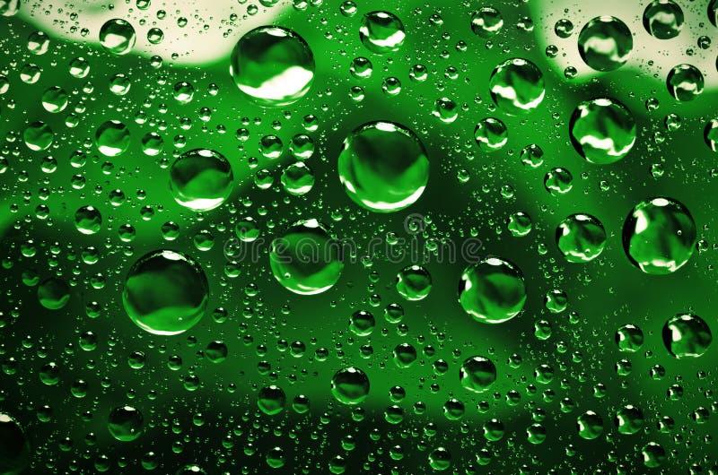 L'eau laisse tomber le fond sur la surface verte Gouttelettes d'eau avec la référence photos libres de droits