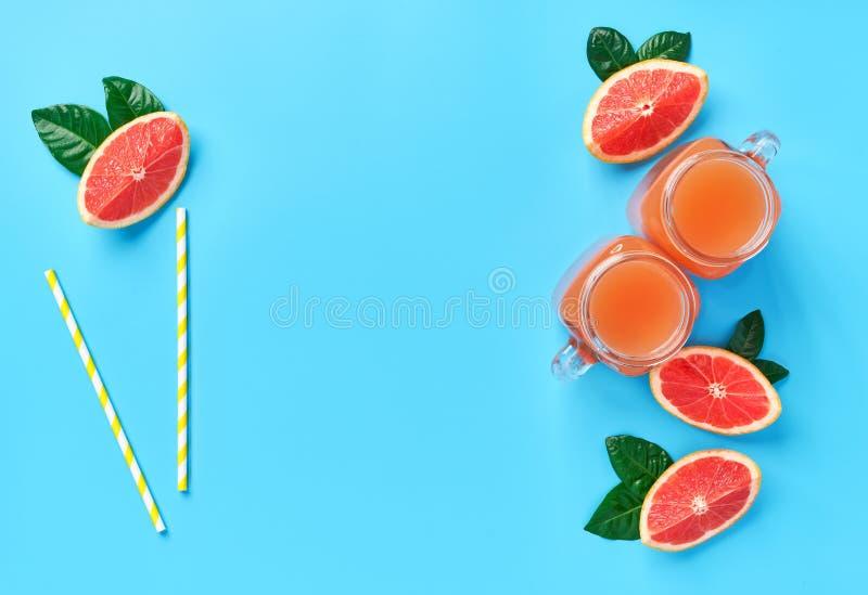 l'eau orange d'été de glace de boissons de citron de carafe Jus de pamplemousse frais sur un fond bleu image libre de droits