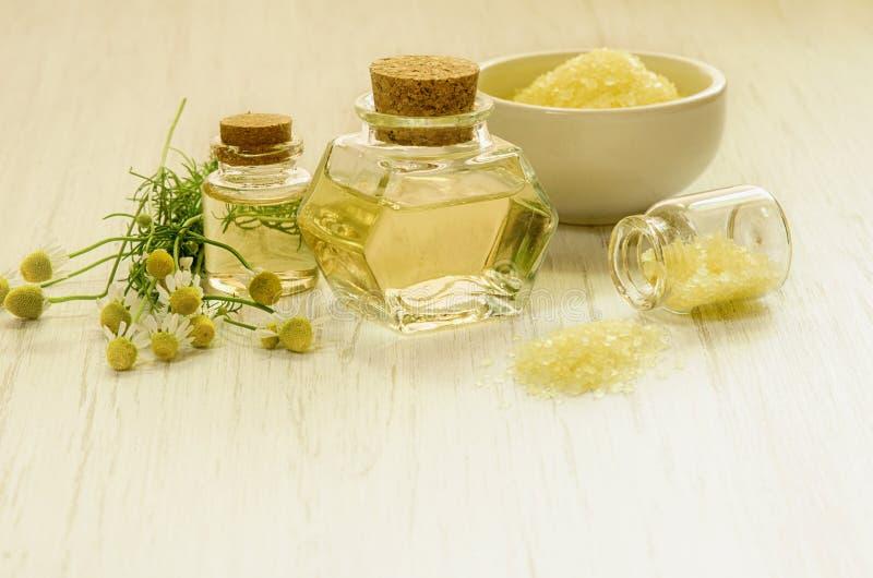 L'eau ou extrait de camomille jaune en bouteilles en verre, sel de station thermale et fleur fraîche avec des feuilles sur le fon photo libre de droits
