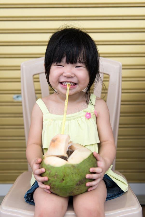 L'eau potable de noix de coco de fille mignonne image libre de droits