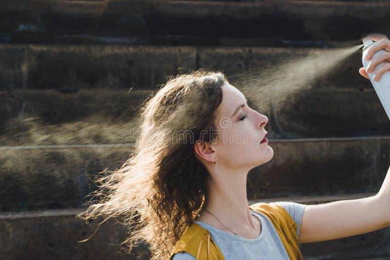 L'eau régénératrice de courant ascendant de dispersion de visage de jeune femme Appréciant, concept de soins de la peau images stock