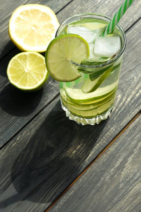 L'eau régénératrice de detox de boissons d'été avec la chaux et la menthe fraîches sur le gris images libres de droits