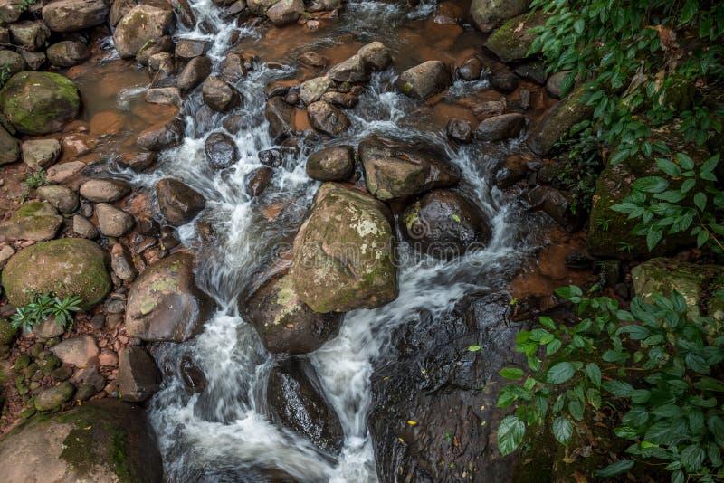 L'eau rapide entrant au-dessus des roches naturelles dans un courant de montagne photographie stock