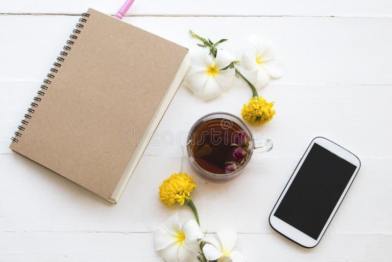 L'eau rose chaude de carnet, de téléphone portable et de cocktail de thé de boissons saines de fines herbes photographie stock libre de droits