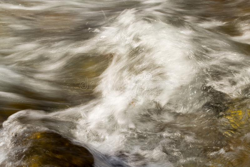 L'eau rugueuse dans l'eau de rivière de montagne comme fond photographie stock libre de droits