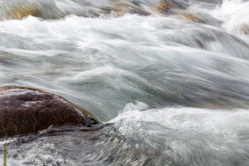 L'eau rugueuse dans l'eau de rivière de montagne comme fond photo stock