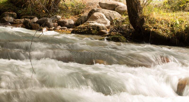 L'eau rugueuse dans l'eau de rivière de montagne comme fond photographie stock