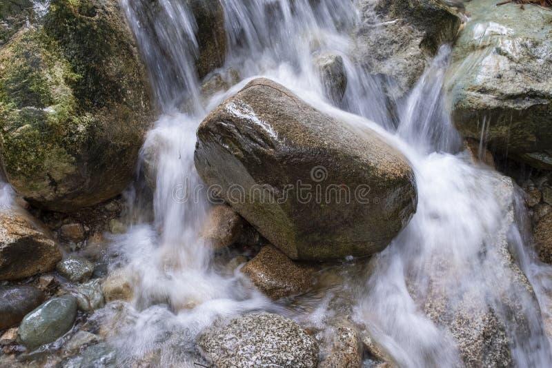 L'eau se précipitant au-dessus d'une grande roche dans un courant photos stock