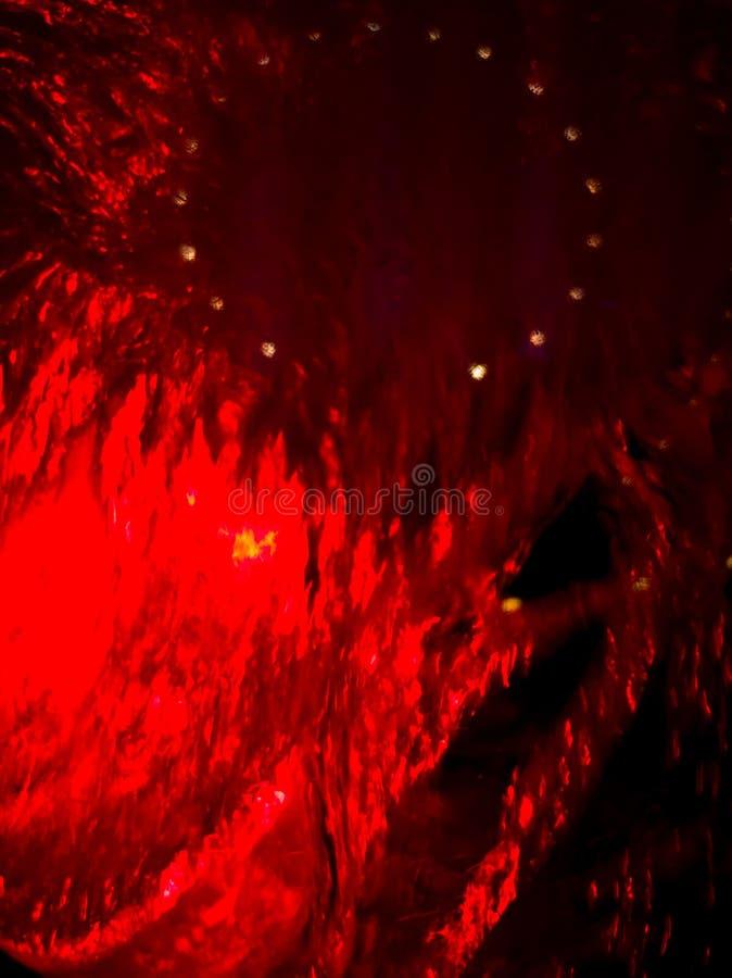 L'eau sous le verre dans la lumière rouge comme fond photographie stock