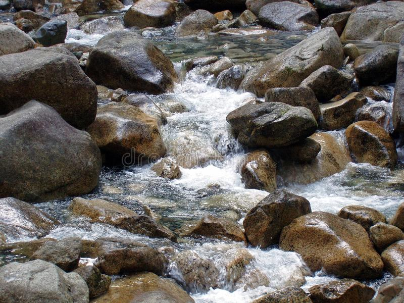 L'eau tombe éclaboussant en bas des roches de sa vue naturelle photos stock