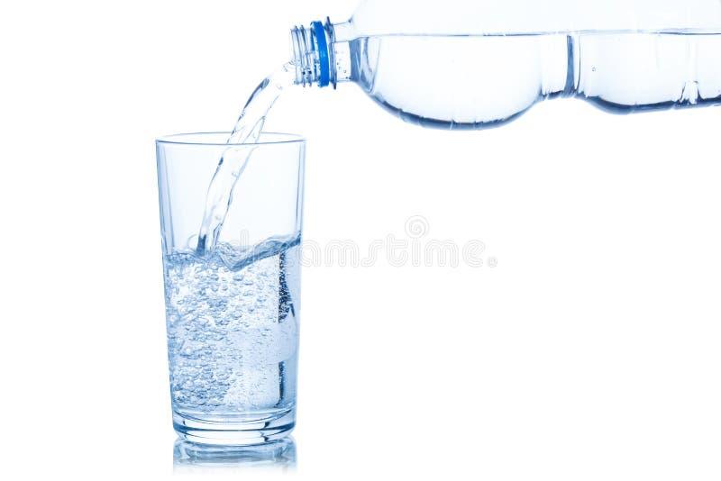 L'eau versant dans la bouteille en verre d'isolement sur le blanc photo stock
