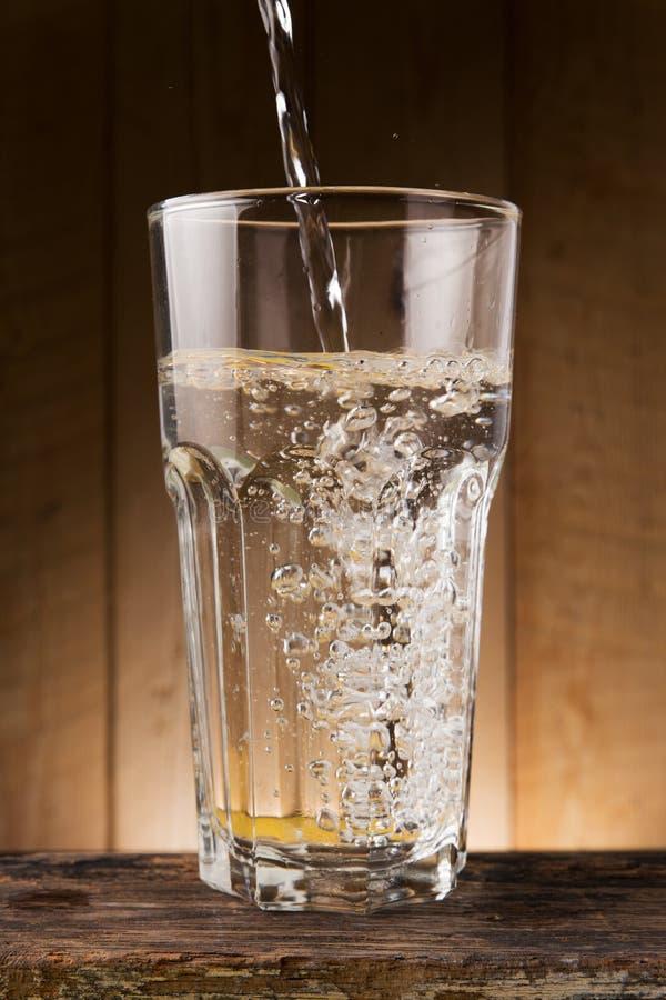 Download L'eau Versent Dessus Au Verre Sur La Table En Bois Photo stock - Image du frais, pétillement: 76084476
