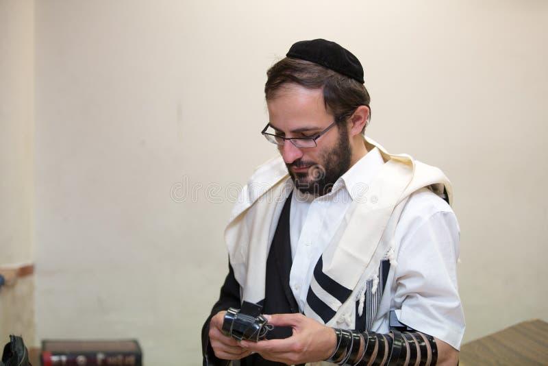 L'ebreo ortodosso pulisce il posto del tefillin dopo le preghiere fotografie stock