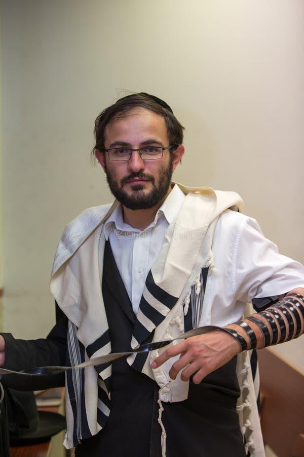 L'ebreo ortodosso pulisce il posto del tefillin dopo le preghiere immagini stock