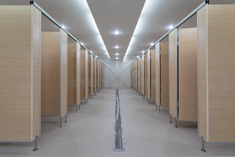L'edificio pubblico è le toilette della donna di prospettiva: parete di legno e porte di legno con downlight luminoso - progettaz fotografie stock libere da diritti