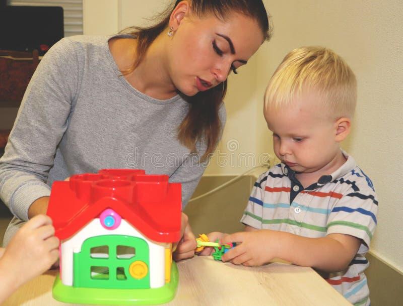 L'educatore tratta con il bambino nell'asilo Creatività e sviluppo del bambino immagine stock