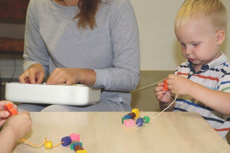 L'educatore tratta con il bambino nell'asilo Creatività e sviluppo del bambino fotografie stock