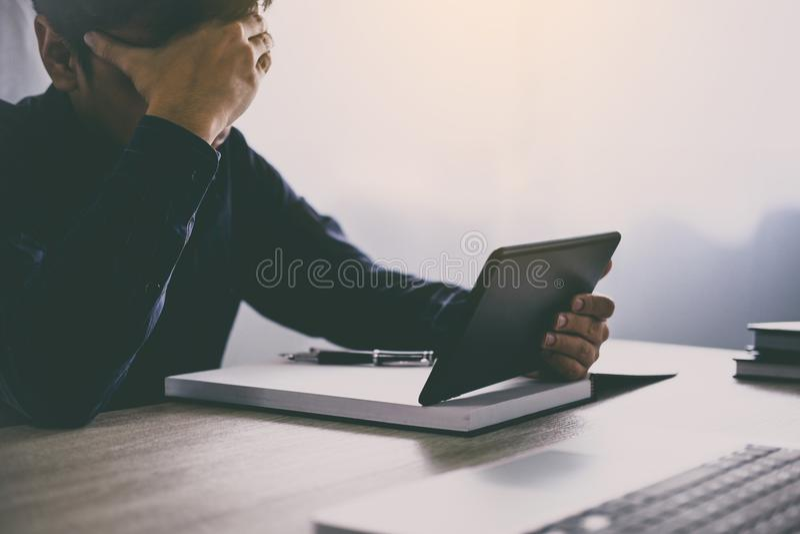 L'effort au travail, homme d'affaires utilisant l'analyse fonctionnante de comprimé investissent images stock