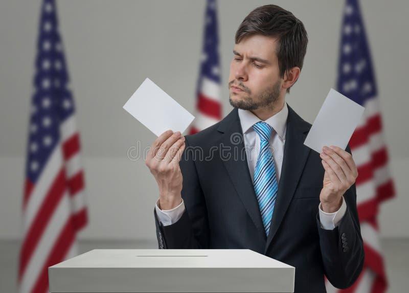L'elettore indeciso tiene le buste in mani sopra il voto di voto fotografia stock libera da diritti