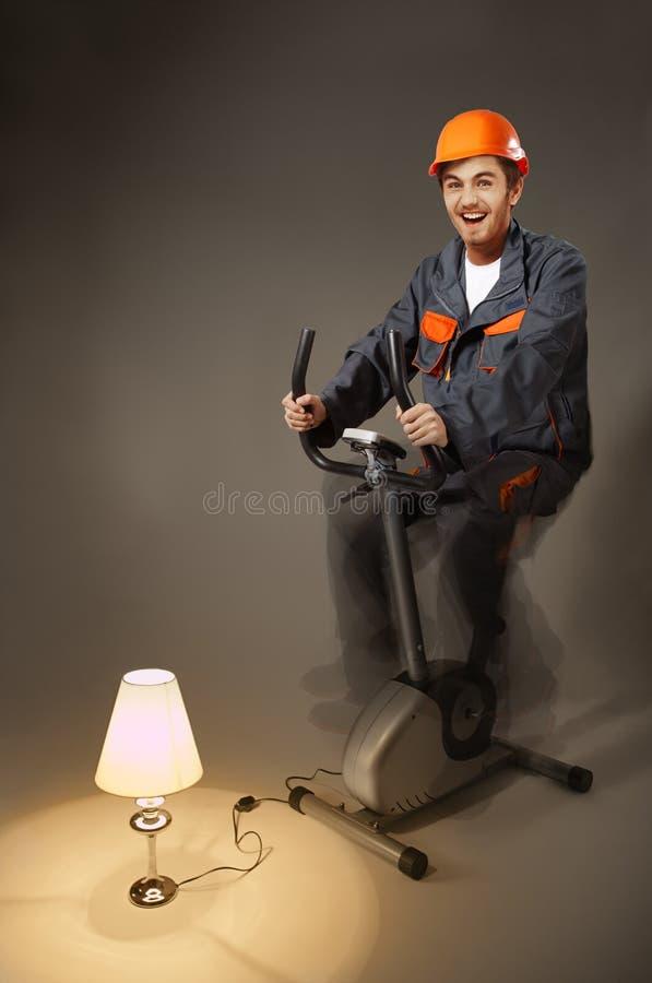 L'elettricista divertente che si siede sulla bici di esercizio genera l'elettricità fotografie stock libere da diritti